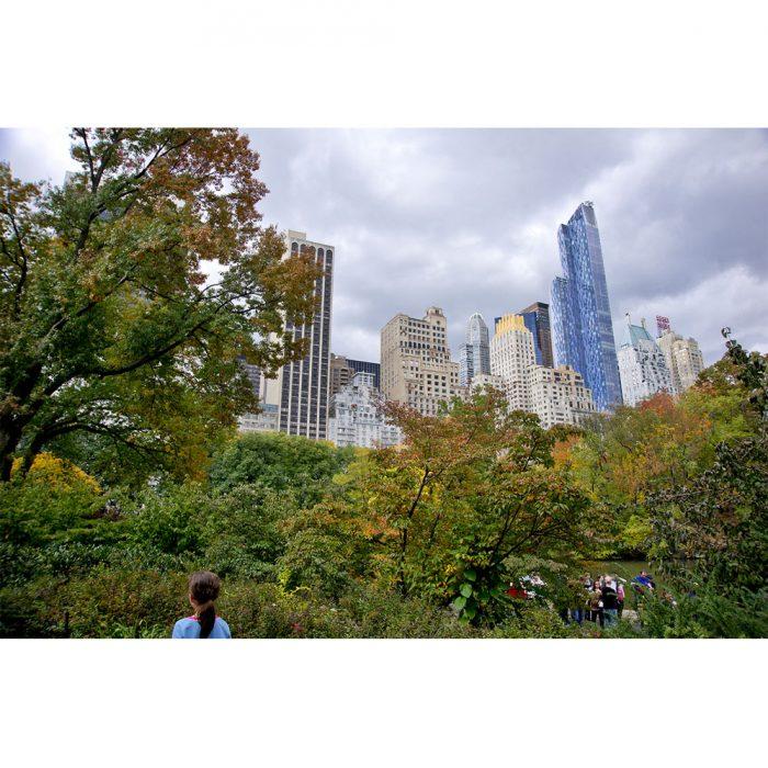 foto de niña observando arboles y edificios en central park de nueva york